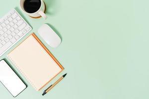 espaço de trabalho mínimo - foto criativa plana da mesa do espaço de trabalho. mesa de escritório de vista superior com teclado, mouse e notebook no fundo da cor verde pastel. vista superior com espaço de cópia, fotografia plana leiga.