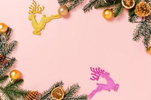 mínima criação plana lay de composição tradicional de Natal e temporada de férias de ano novo. vista superior decorações de Natal de inverno em fundo rosa com espaço em branco para texto. copie a fotografia do espaço. foto