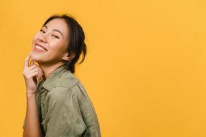 jovem asiática com expressão positiva, sorriso largo, vestida com roupas casuais e olhando para a câmera sobre fundo amarelo. feliz adorável feliz mulher alegra sucesso. conceito de expressão facial. foto