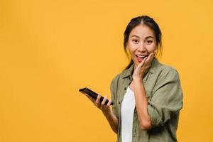 surpreendeu a jovem asiática usando telefone celular com expressão positiva, sorria amplamente, vestida com roupas casuais e olhando para a câmera sobre fundo amarelo. feliz adorável feliz mulher alegra sucesso. foto