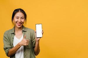 jovem senhora asiática mostra tela vazia do smartphone com expressão positiva, sorri amplamente, vestida com roupas casuais, sentindo felicidade sobre fundo amarelo. telefone celular com tela branca na mão feminina. foto