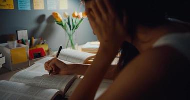 jovem ásia adolescente menina estudante lição de aprendizagem à distância e fazendo lição de casa sentado na mesa na sala de estar à noite em casa. trabalho de casa, distanciamento social, quarentena para prevenção do vírus corona. foto