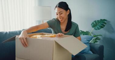 feliz senhora asiática abrir pacote de caixa de papelão emocionante e desfrutar de experimentar e combinar com a qualidade do produto de pano da moda do mercado online na sala de estar em casa. conceito de compras e entrega online. foto