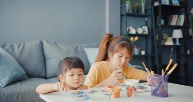 feliz alegre mãe de família asiática ensinar menina criança pintar pote de cerâmica se divertindo, relaxar na mesa na sala de estar em casa. passar tempo juntos, distância social, quarentena para prevenção do coronavírus. foto