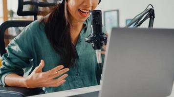 menina asiática feliz gravar um podcast em seu laptop com fones de ouvido e microfone falar com o público em seu quarto. podcaster feminino fazer podcast de áudio de seu estúdio em casa, conceito de ficar em casa. foto