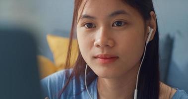 jovem adolescente asiática com fones de ouvido de uso casual, usar o computador portátil, aprender on-line, escrever o caderno de aula na sala de estar em casa. isolar o conceito de pandemia de coronavírus de e-learning de educação on-line. foto