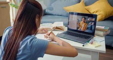 jovem asiática com videochamada de laptop de computador de uso casual aprender on-line com a sala de estar do professor escrever palestra em casa. isolar o conceito de pandemia de coronavírus de e-learning de educação on-line. foto