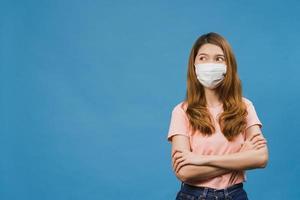 jovem asiática usando máscara médica com vestido de pano casual e olhando para o espaço em branco isolado sobre fundo azul. auto-isolamento, distanciamento social, quarentena para prevenção do vírus corona foto