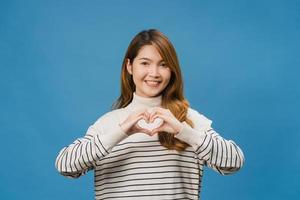 jovem senhora asiática com expressão positiva, mostra gesto de mãos em forma de coração, vestida com roupas casuais e olhando para a câmera isolada sobre fundo azul. feliz adorável feliz mulher alegra sucesso. foto