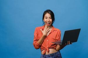 surpreendeu a jovem asiática usando laptop com expressão positiva, sorriso largo, vestido com roupas casuais e olhando para a câmera sobre fundo azul. feliz adorável feliz mulher alegra sucesso. foto