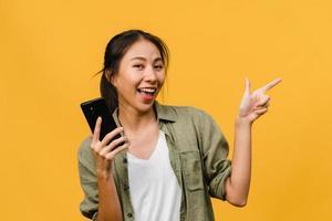 jovem senhora asiática usando telefone celular com expressão alegre, mostra algo incrível no espaço em branco em um pano casual e olhando para a câmera isolada sobre fundo amarelo. conceito de expressão facial. foto
