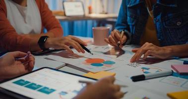 millennial asia people meeting brainstorming ideas sobre a nova papelada projeto colegas trabalhando juntos planejam a estratégia de sucesso desfrutar o trabalho em equipe em um pequeno e moderno escritório noturno. conceito de trabalho em equipe do colega. foto