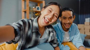 feliz jovem casal asiático, homem e mulher se sentam no sofá, olhando para a videochamada da câmera com amigos e familiares na sala de estar em casa. ficar em casa quarentena, distanciamento social, conceito de jovem casado. foto