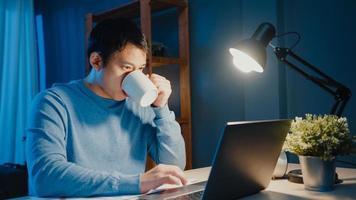empresário asiático faça uma pausa com uma xícara de café relaxe e verifique a atribuição de trabalho no computador portátil para a agenda na sala de estar em casa horas extras à noite, trabalho em casa conceito de pandemia de corona. foto