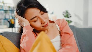 linda senhora asiática sentir relaxar deitar no sofá com o travesseiro em casa. fique em casa, faça uma pausa no trabalho, relaxe na zona de conforto em casa, descanse um pouco em casa, mantenha distância, conceito de quarentena ambicioso. foto