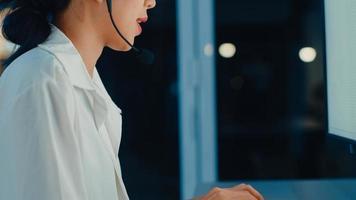 jovem milenar asiático agente de call center ou executivo de serviço de suporte ao cliente usando computador e fone de ouvido com microfone trabalhando no suporte técnico tarde da noite no escritório. conceito de trabalho de telemarketing ou vendas. foto