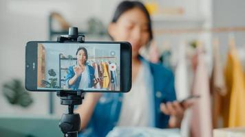designer de moda jovem asiática usando telefone celular, recebendo pedido de compra e mostrando roupas, gravando vídeo com transmissão ao vivo online na loja. proprietário de uma pequena empresa, conceito de entrega de mercado online. foto