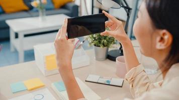 jovem asiática usar telefone inteligente com simulação de tela preta em branco para texto de publicidade enquanto inteligente trabalhando em casa na sala de estar. tecnologia chroma key, conceito de design de marketing. foto