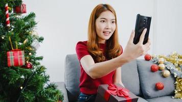 jovem mulher asiática usando videochamada de telefone inteligente falando com casal com caixa de presente de Natal, árvore de Natal decorada com enfeites na sala de estar em casa. festival de férias de Natal e ano novo. foto