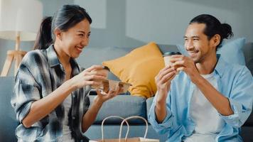 feliz asiático jovem casal atraente homem e mulher sentar-se na nova casa, beber café, relaxar e conversar, sorrir com armazenamento de caixa de pacote da caixa para se mudar para a nova casa. jovem asiático se casou com o conceito de casa. foto