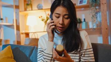 mulher asiática jovem doente segurar remédio sentar no sofá usar telefone inteligente para consultar o médico em casa à noite. garota tomar remédio após ordem do médico, quarentena em casa, conceito de coronavírus de distância social. foto
