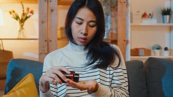 doente jovem asiática segurando a pílula dê uma olhada medicina sentar no sofá em casa à noite. garota tomando remédio após ordem do médico, quarentena em casa, conceito de saúde de distanciamento social de coronavírus. foto