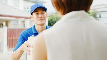 jovem Ásia entrega postal homem de camisa azul manuseio de caixas de pacotes para envio ao cliente em casa e mulher asiática recebe pacote entregue ao ar livre. conceito de entrega de comida de compras de pacote. foto
