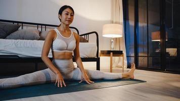 jovem asiática no sportswear fazendo exercícios de ioga malhando na sala de estar em casa à noite. atividade de esporte e recreação, distanciamento social, quarentena para o conceito de prevenção do vírus corona. foto