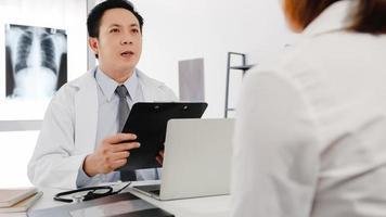 Médico sério da Ásia em uniforme médico branco, usando a área de transferência, está entregando uma ótima palestra, discute os resultados ou sintomas com uma paciente sentada à mesa na clínica de saúde ou no escritório do hospital. foto