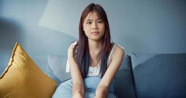 jovem feliz Ásia adolescente garota com alegre relaxar tempo sorrindo, olhando para a câmera na sala de estar em casa. isolar o estilo de vida da atividade, o conceito de pandemia de coronavírus de distância social. foto
