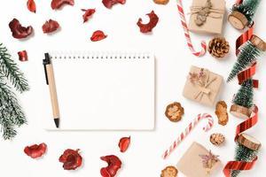 mínima criativa plana lay de composição tradicional de natal de inverno e temporada de férias de ano novo. vista superior caderno preto de maquete aberta para texto em fundo branco. mock up e cópia da fotografia do espaço. foto