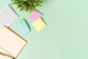 foto plana leiga criativa da mesa do espaço de trabalho. mesa de escritório de vista superior com teclado, mouse e caderno preto de maquete aberta sobre fundo de cor verde pastel. vista superior simulada com fotografia do espaço da cópia.