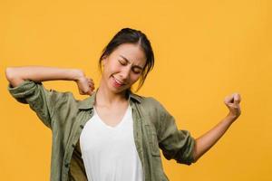 jovem asiática com expressão positiva, alegre e emocionante, vestida com um pano casual sobre fundo amarelo com espaço vazio. feliz adorável feliz mulher alegra sucesso. conceito de expressão facial. foto
