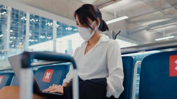 O viajante asiático da senhora de negócios usa máscara facial, sentado no banco, usa o laptop para trabalhar entre a espera pelo voo no terminal do aeroporto. viajante de negócios em uma pandemia covid, conceito de viagens de negócios. foto