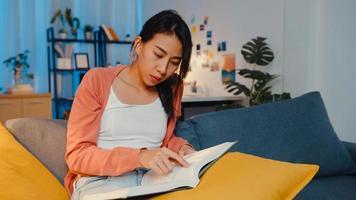 à noite, a bela senhora asiática leu o livro com felicidade na pacífica sala de estar no sofá. educação em casa, ficar em casa, atividade de auto-quarentena, atividade divertida para quarentena de covid ou coronavírus. foto
