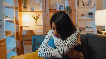 senhora asiática pensativa, sofrendo de insônia, sente-se no sofá na sala de estar à noite em casa com a sensação de solidão, adolescente deprimido e triste, passar um tempo sozinho ficar em casa, distância social, quarentena de coronavírus. foto