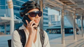 empresária asiática com conversa de celular de chamada de mochila sorrindo na rua da cidade ir trabalhar no escritório. garota de esportes usa seu telefone para trabalhar no negócio. comuta para o trabalho de bicicleta, viajante de negócios na cidade. foto