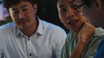 jovens empresários e mulheres de negócios asiáticos felizes reunindo-se e debatendo algumas novas idéias sobre o projeto para seu parceiro trabalhando juntos planejando uma estratégia de sucesso, desfrute do trabalho em equipe em um pequeno e moderno escritório noturno. foto