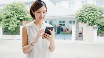atraente jovem empresária da Ásia usando telefone celular, verificando a internet de mídia social, conversando com amigos do lado de fora na rua da cidade. estilo de vida novo normal após coronavírus e distanciamento social. foto