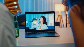 jovem ásia mulher bebendo cerveja se divertindo momento feliz noite festa evento on-line celebração via videochamada na sala de estar em casa à noite. distanciamento social, quarentena para prevenção de coronavírus. foto
