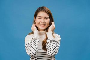 jovem asiática com expressão positiva, sorriso largo, vestida com roupas casuais e olhando para a câmera sobre fundo azul. feliz adorável feliz mulher alegra sucesso. conceito de expressão facial. foto