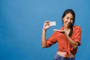 jovem senhora asiática mostra cartão de crédito com expressão positiva, sorri amplamente, vestida com roupas casuais, sentindo felicidade e carrinho isolado sobre fundo azul. conceito de expressão facial. foto