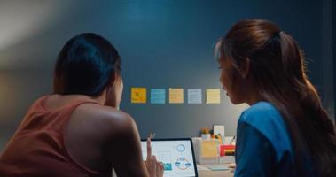 horas extras trabalhando mulher asiática usando tablet veja o gráfico na mesa conversar com colegas sobre o plano de estratégia de finanças do trabalho no escritório em casa à noite. auto-isolamento, distanciamento social, quarentena para coronavírus. foto