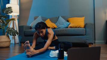 jovem asiática em exercícios de sportswear fazendo exercícios e usando o laptop para assistir a um vídeo tutorial de ioga em casa à noite. treinamento à distância com personal trainer, distância social, conceito de educação online. foto