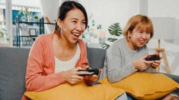 casal de mulheres lésbicas LGBTQ joga videogame em casa. jovem senhora asiática usando o controlador sem fio, tendo o momento engraçado e feliz juntos no sofá na sala de estar. eles se divertem muito celebrando o feriado. foto