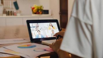 empresária asiática usando tablet digital conversa com um colega sobre plano por videochamada brainstorm reunião on-line enquanto trabalha remotamente de casa na cozinha. distanciamento social, quarentena para o vírus corona. foto