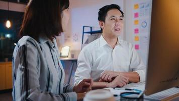 grupo de empresário e mulher de negócios da Ásia usando apresentação de computador e reunião de comunicação de brainstorming de idéias sobre novos colegas de projeto trabalhando estratégia de sucesso de plano no escritório em casa à noite. foto