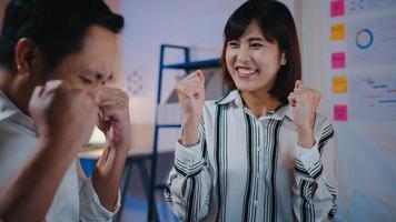 grupo de empresário e mulher de negócios da Ásia em negócios de discussão casuais comemora dando cinco depois de lidar com o sentimento de felicidade e assinar o contrato ou acordo no escritório à noite. conceito de trabalho em equipe de colega de trabalho foto