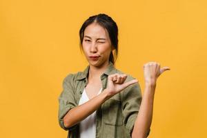 retrato de uma jovem asiática sorrindo com uma expressão alegre, mostra algo incrível no espaço em branco em um pano casual e olhando para a câmera isolada sobre fundo amarelo. conceito de expressão facial. foto