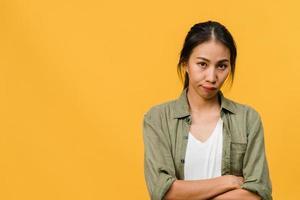 jovem asiática com expressão negativa, animado gritando, chorando emocionalmente com raiva em roupas casuais e olhar para a câmera isolada em um fundo amarelo com espaço de cópia em branco. conceito de expressão facial foto